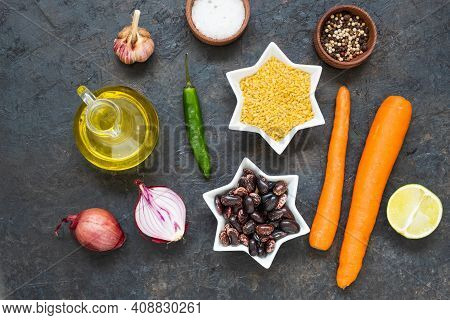 Prepared Ingredients For Cooking Bulgur Saw With Carrots And Black Beans On A Black Concrete Backgro