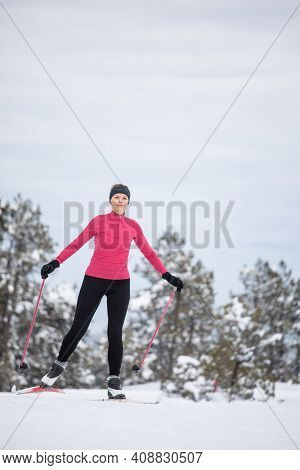 Cross-country skiing: young woman cross-country skiing on a winter day