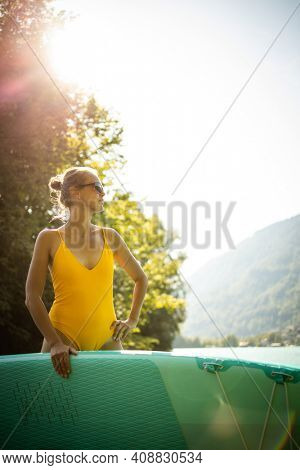 Pretty, young woman paddling on a paddle board on a lake, enjoying a lovely summer day