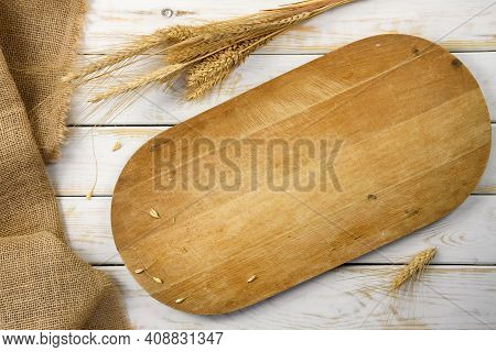 Rustic Baking Template - Top View Of An Empty Wooden Cutting Board With Cereal Grains And Burlap Sac
