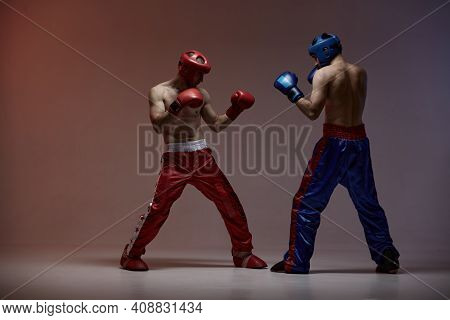 Wrestling Of Two Fighting Males In Helmets And Boxing Gloves In Red Light In Studio, Martial Arts, M