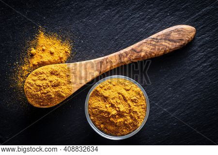 Indian turmeric powder. Turmeric spice. Ground turmeric in wooden spoon. Top view.