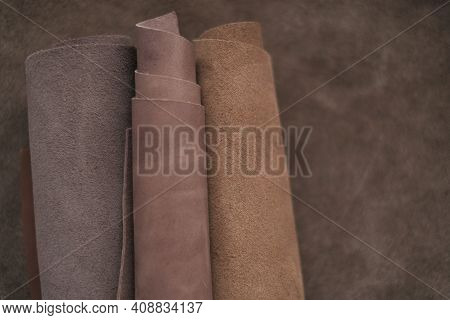 Brown Genuine Leather Roll.real Leather Set. Leather In Rolls On A Brown Leather Surface.hobby And C
