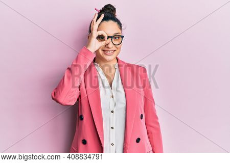 Beautiful middle eastern woman wearing business jacket and glasses doing ok gesture with hand smiling, eye looking through fingers with happy face.