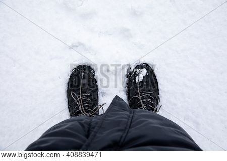 Womens Feet In The Black Boots On The Snow-top View.