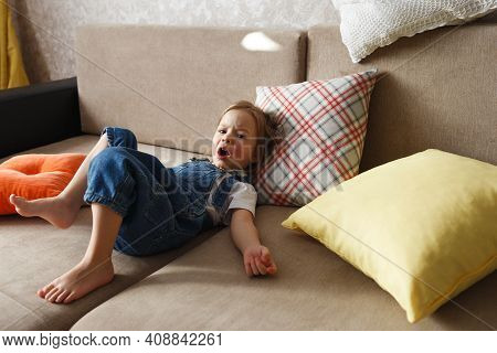 A Little Girl In A Blue Jumpsuit Is Lying At Home On The Sofa Among The Colorful Pillows With A Diss