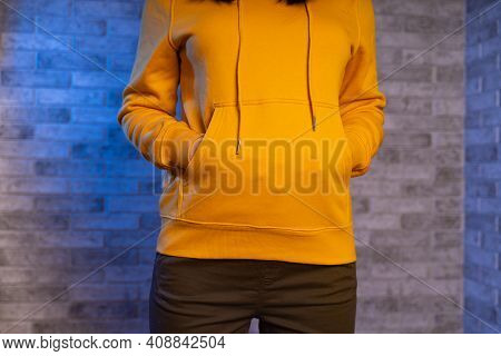 Close Up Of Woman's Hands Of Unrecognizable Person In Pockets Of Yellow Hoodie On Gray Brick Backgro