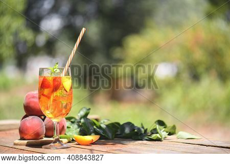 Fresh Homemade Peach Sweet Tea With Mint And Peach Slices, Summer Cold Fruit Drink Outdoors. Colorfu