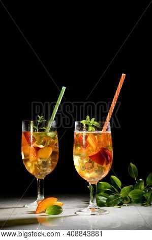 Peach Fresh Tea With Ice, Peach Summer Mocktail On A Black Background. Amber Wine, Sangria With Peac