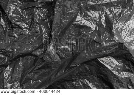Black Texture Of Crumpled Wrinkled Garbage Plastic Bag. Abstract Background