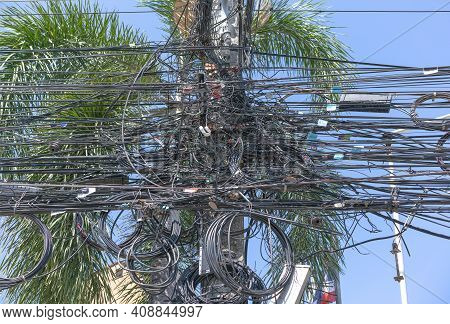 Chaos Of Cables And Wires On An Electric Pole. Many Electrical Cable - Wire And Telephone Line On El
