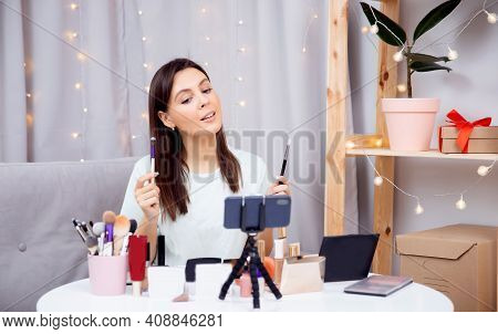 Concept Influencer Blogger Beauty Blog. Happy Woman Vlogger Is Showing Cosmetics Products While Reco