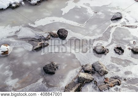 Close Up Picture Of Frozen Water With Stones In The River. Bubbles In The Icy Water. Natural Texture