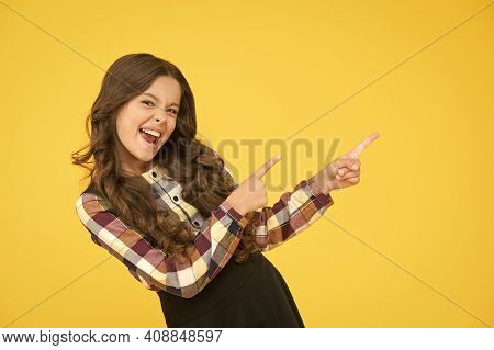 Dont Leave Without It. Happy Child Pointing At Yellow Background. Little Kid With Pointing Gesture.