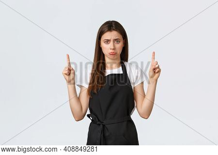 Small Business, Employees And Coffee Shop Concept. Gloomy And Sad Cute Waitress Pointing Fingers Up