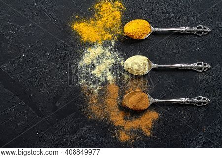 Different Kind Of Spices On A Black Stone. Oriental Spices In Spoons, Cinnamon, Turmeric, Ginger. Fl