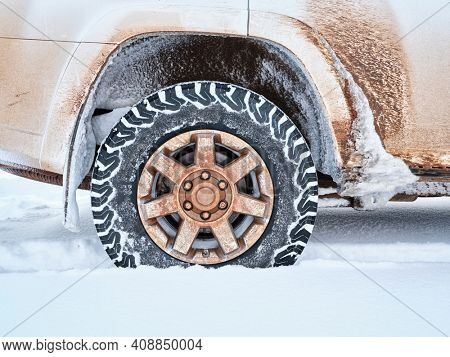 Closeup of all-terrain tire and wheel of dirty 4x4 SUV car or truck  - winter travel and recreation concept