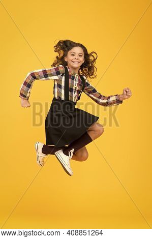Day Full Of Fun. Happy Child Enjoy Happiness. Energetic Girl In Midair Yellow Background. Childhood