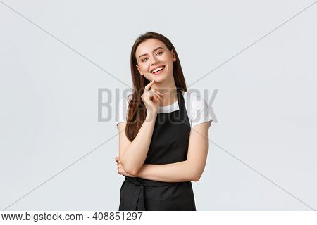 Small Business, Employees And Coffee Shop Concept. Cheerful Pretty Store Clerk In Black Apron Laughi