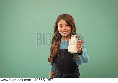 I Offer This. Little Girl Showing Cream Plastic Bottle. Products For Children. Kids Multivitamins In