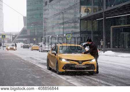 Moscow. Russia. February 12, 2021. The Driver Of The Yellow Taxi Car Cleans The Windshield And Wiper