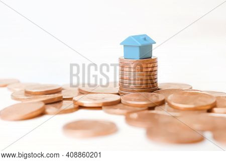 Blue Toy House Money Coins Stack On White Background. Mini House Model On Stack Coins Pile Money Hom
