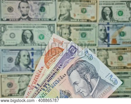 Approach To Honduran Banknotes And Background With American Dollar Bills