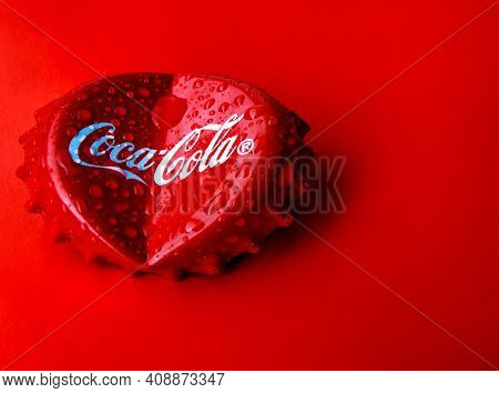 Krasnoyarsk, Russia - January 23, 2021: Iron Cap Coca-cola On A Red Background. A Heart From A Bent