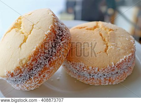 Closeup A Pair Of Delectable Alfajores, Traditional Latin American Sweets On A White Plate