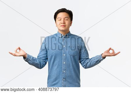 Relieved And Relaxed Smiling Asian Man With Closed Eyes Meditating, Feeling Peaceful And Happy, Rele