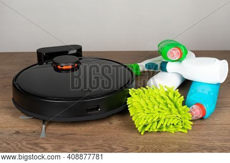 Picture Of An Automatic Intelligent Robotic Vacuum Cleaner  And  Colorful Cleaning Product On The Fl
