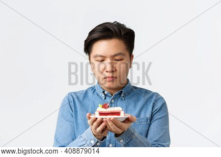 Close-up Of Gloomy Asian Guy Tempting To Try Piece Cake, Looking At Dessert With Desire. Man On Diet