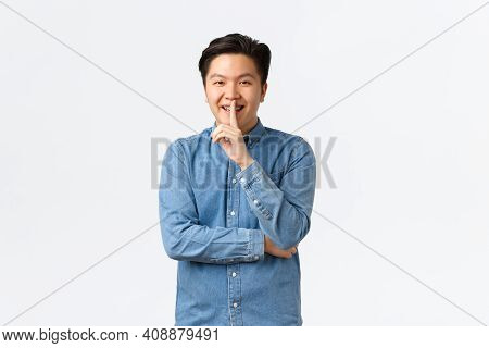 Smiling Cunning Asian Man Preparing Surprise, Asking Keep Quiet, Shushing Or Hushing At Person, Pres