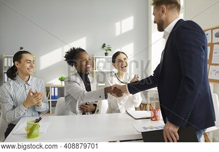 Young Multiracial Business Team Shakes Hands With A Man Welcoming Him As A New Team Member.