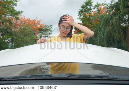 Young Stressed Woman Having Trouble With Her Car Breakdown On The Road And She Opening Car Hood For
