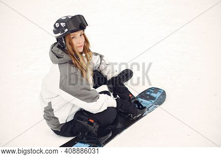 Girl Snowboarding In The Mountains With The Snowboard