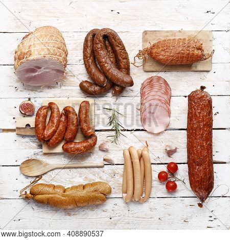 A Rustic Composition Of Homemade, Smoked Cold Cuts. Ham, Sausages, Wieners On Light Wooden Boards, D