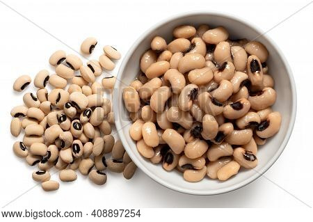 Cooked Black-eyed Beans In A White Ceramic Bowl Next To Uncooked Black-eyed Beans Isolated On White.