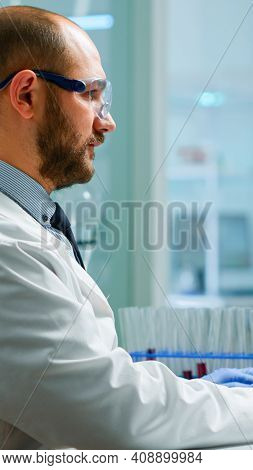 Scientist In Lab Coat Analysing Blood Sample From Test Tube. Viorolog Researcher In Professional Lab