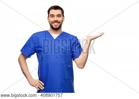 healthcare, profession and medicine concept - happy smiling doctor or male nurse in blue uniform holding something imaginary on empty hand over white background