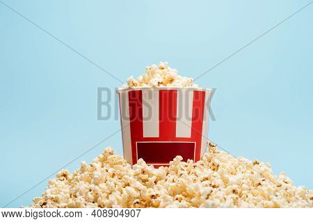 Striped Paper Bucket With Crunchy Popcorn Isolated On Blue, Cinema Concept.