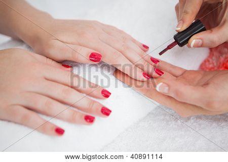 Close-up of woman applying nail varnish to finger nails at nail salon