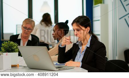 Concentrated Manager Typing On Laptop Sitting At Desk In Start Up Business Office Drinking Coffee Wh