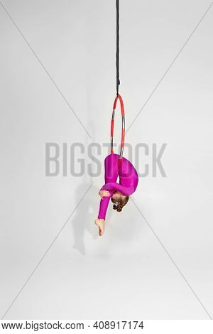 Little Child Girl Gymnast In Pink Sportwear Doing Acrobatic Tricks On An Aerial Hoop