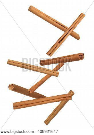 Aromatic Cinnamon Sticks Falling On White Background