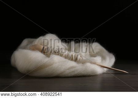 Soft White Wool With Spindle On Wooden Table Against Black Background