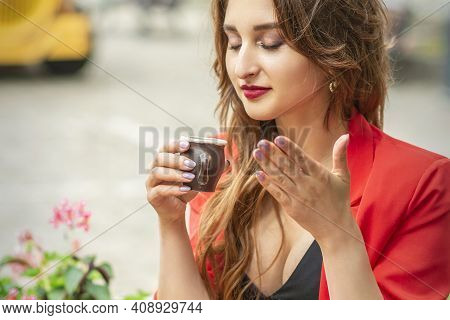 Beautiful Young Woman Sniffing Coffee In A Small Cup And Drinking Coffee Sitting At The Table In A C