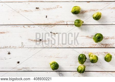 Set Of Brussel Sprouts On White Wooden Table. Top View. Copy Space