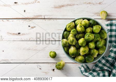 Set Of Brussel Sprouts In A Bowl On White Wooden Table. Top View. Copy Space