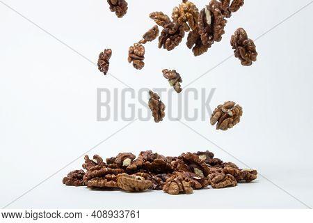 Peeled Walnuts On A White Background. A Peeled Walnut Falls Down Onto A Pile Of Walnuts. Nutritious